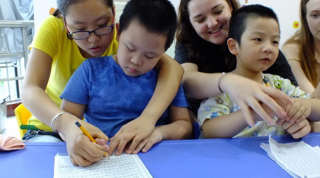 Twee vrouwelijke Kinderopvang vrijwilligers werken met kidneren in China en helpen twee kinderen met Engelse schrijfvaardigheid in een kleuterschool.